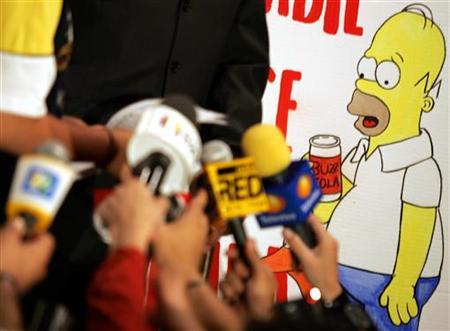 Mexican actors hold up paintings of characters from the Simpsons cartoon as local media hold up microphones during a protest in Mexico City August 3, 2005. REUTERS/Daniel Aguilar
