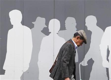 A man walks past an advertisement signboard at a shopping district in Tokyo, October 1, 2010. REUTERS/Kim Kyung-Hoon