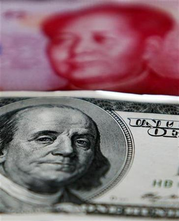 A yuan banknote is displayed behind a U.S. dollar banknote for the photographer at a money changer inside the Taoyuan International Airport March 18, 2010.REUTERS/Nicky Loh