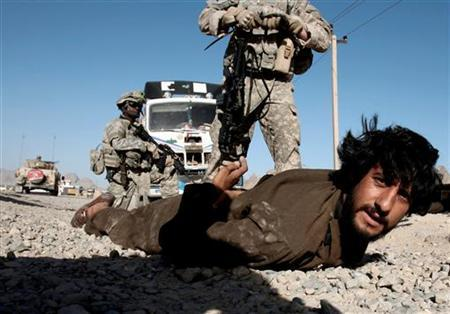 U.S. soldiers search for weapons on an Afghan man, who works for a private security firm escorting truck convoys, after they found illegal weapons in his vehicle, in a village near Kandahar in this April 27, 2008 file photo. REUTERS/Goran Tomasevic/Files