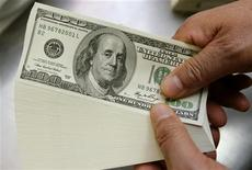 <p>A bank employee poses holding U.S. one hundred dollar notes during a photo opportunity at a bank in Seoul November 19, 2009. REUTERS/Choi Bu-Seok</p>