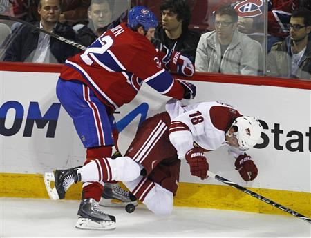 Montreal Canadiens Travis Moen sends Phoenix Coyotes Sami Lepisto crashing into the boards during the second period of their NHL hockey game in Montreal, October 25, 2010. Moen was given a boarding penalty on the play. REUTERS/Shaun Best