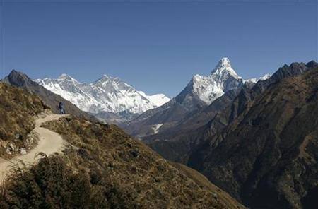 A tourist (L) looks at a view of Mount Everest from the hills of Syangboche in Nepal December 3, 2009. REUTERS/Gopal Chitrakar