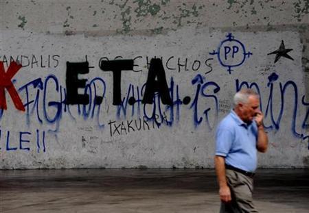 A man walks past ETA graffiti in Mondragon September 6, 2010. REUTERS/Vincent West