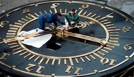 <p>Механики проверяют работу гигантских часов на административном здании в Красноярске, 8 сентября 2001 года. В ночь с субботы на воскресенье Россия и еще пять стран СНГ перейдут на зимнее время. REUTERS/Ilya Naimushin</p>