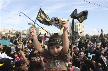 A Palestinian girl waves Islamic Jihad flags during a rally in Gaza City October 29, 2010. Thousands of Palestinians attend a rally marking the 23rd anniversary of the Islamic Jihad movement foundation. REUTERS/Mohammed Salem