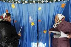 <p>Женщины выходят из кабинок для голосования на избирательном участке в деревне Мужичи, пригород Киева 31 октября 2010 года.Состоявшиеся в воскресенье местные выборы на Украине расширили влияние на регионы партии Виктора Януковича, получившего по решению суда в начале октября всю полноту президентской власти. REUTERS/ Konstantin Chernichkin</p>