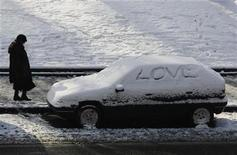 <p>A woman walks by a car covered in snow in Madrid January 11, 2010. REUTERS/Susana Vera</p>