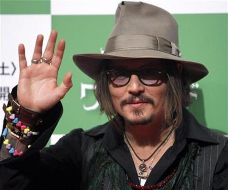 Actor Johnny Depp waves at a photo session to promote the movie ''Alice in Wonderland'' in Tokyo March 22, 2010. REUTERS/Toru Hanai