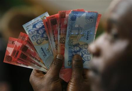 A man holds Ghana's cedi notes in Accra July 3, 2007. REUTERS/Luc Gnago