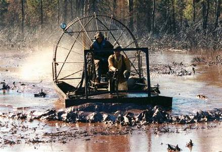 Russian workers riding an airboat clean up an oil slick in the river Kolva near the Russian town of Usinsk in this August 16, 1995 file photo. REUTERS/Gennady Galperin/Files