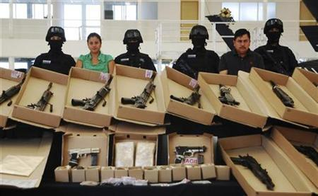 Mexican federal police present two suspected members of the Los Zetas drug cartel and weapons confiscated during their capture at a news conference at the federal police center in Mexico City October 22, 2010. REUTERS/Mexican Federal Police/Handout