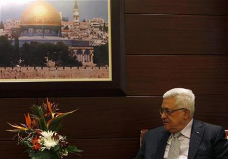Palestinian President Mahmoud Abbas sits under a picture of the Dome of the Rock during a meeting with Middle East envoy Tony Blair (not seen) in the West Bank city of Ramallah October 19, 2010. REUTERS/Mohamad Torokman