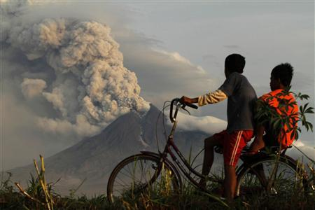 Boys look at the eruption of Mount Merapi volcano in Manisrenggo village, in the Klaten district of Indonesia's central Java province November 10, 2010. REUTERS/Andry Prasetyo