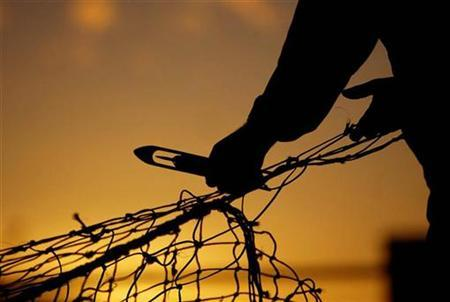 A file photo shows fisherman repairing his net as the sun sets on Peterhead harbour in Scotland. REUTERS/files