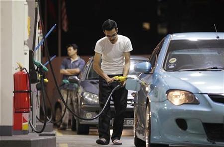 A motorist pumps petrol at a gas station in Kuala Lumpur July 15, 2010. REUTERS/Bazuki Muhammad