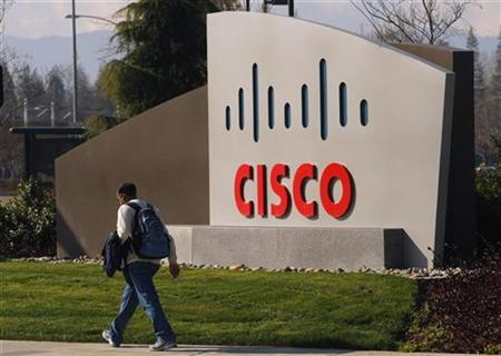 A pedestrian walks past the Cisco logo at the technology company's campus in San Jose, California in this February 3, 2010 file photo. REUTERS/Robert Galbraith