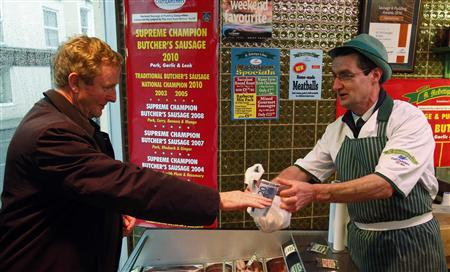 Ireland's Leader of the Opposition Enda Kenny of the Fine Gael party (L) buys sausages from a butcher while on a campaign stop for local Donegal south west candidate Councillor Barry O'Neill in Donegal, Ireland November 11, 2010 REUTERS/Cathal McNaughton