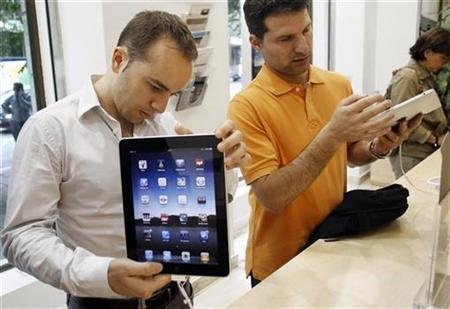 Visitors check out the new Apple iPads at an Apple retail store in Madrid in this May 28, 2010 file photo. REUTERS/Susana Vera