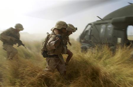 U.S. Marines help their wounded comrade to a helicopter while under fire during a Medevac mission in southern Afghanistan's Helmand Province November 10, 2010. REUTERS/Peter Andrews