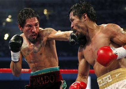 Manny Pacquiao (R) of the Philippines is punched by Antonio Margarito of Mexico during the 10th round of their 12-round WBC World Super Welterweight title boxing fight in Arlington, Texas November 13, 2010. REUTERS/Mike Stone