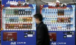 <p>A man walks past vending machines of Asahi Soft Drinks in Tokyo December 1, 2008. REUTERS/Stringer</p>