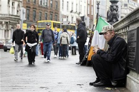 A beggar sits on O'Connell Bridge in the centre of Dublin, Ireland October 2, 2010. REUTERS/Cathal McNaughton