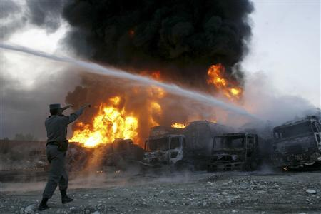 An Afghan policeman gestures as trucks carrying fuel for NATO forces burn in Behsud district of Nangarhar province November 14, 2010. Insurgents set fire to 12 fuel tankers carrying fuel for NATO forces in Afghanistan on early Sunday morning, a local official said. REUTERS/ Parwiz