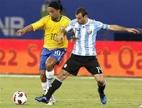 <p>Ronaldinho tenta se livrar da marcação do argentino Javier Mascherano no amistoso Brasil x Argentina em Doha, no Catar. 17/11/2010 REUTERS/Fadi Al-Assaad</p>