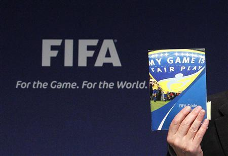 FIFA Ethics Committee Chairman Claudio Sulser displays a copy of FIFA's Code of Ethics during news conference after the meeting of the Ethics Committee at the Home of FIFA in Zurich November 18, 2010. REUTERS/Christian Hartmann