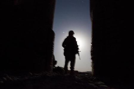 A U.S. Marine waits in the moonlight for a helicopter to transport him home for leave from Musa Qala in southern Afghanistan's Helmand province, November 16, 2010. REUTERS/Finbarr O'Reilly