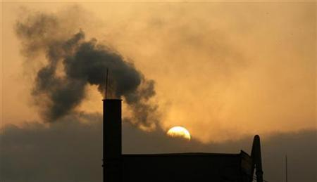 A sunset is seen in the background of a chimney of a concrete factory in Hanoi, Vietnam, April 19, 2010. REUTERS/Kham