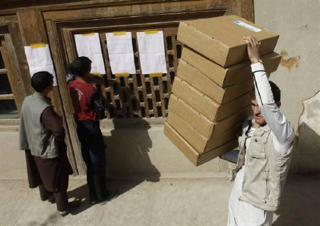 Representatives of candidates check the results as a worker removes the election materials at a polling station in Kabul September 19, 2010. REUTERS/Andrew Biraj/Files