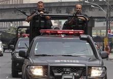 <p>Policiais patrulham rua durante operação na Vila Cruzeiro, cinco dias após atos criminosos: comitês da Copa-2014 e do Rio-2016 confiam no plano de segurança para a cidade. REUTERS/Sergio Moraes</p>