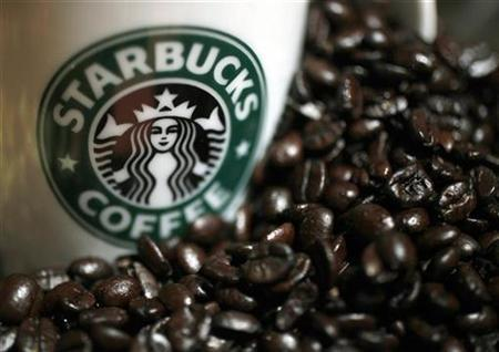 A mug bearing a Starbucks logo is pictured next to coffee beans during a news conference in Tokyo April 13, 2010. REUTERS/Yuriko Nakao