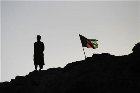 An Afghan policeman stands beside the national flag while watching a patrol return to base from a clifftop near the town of Kunjak in southern Afghanistan's Helmand province, November 1, 2010. REUTERS/Finbarr O'Reilly