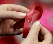 <p>Estudante faz o laço vermelho da Aids durante evento do dia Mundial da Aids em Pequim, 1o de dezembro de 2010. REUTERS/Jason Lee</p>