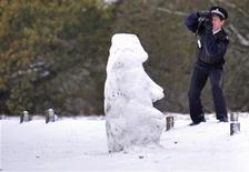 <p>A Parks Police officer takes photographs of a snowman in Richmond Park in south west London December 1, 2010. REUTERS/Toby Melville</p>