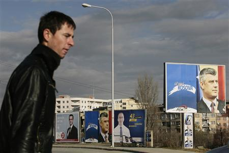 A man walks past election posters in the capital Pristina December 6, 2010. Parliamentary elections will be held on December 12, 2010. REUTERS/Hazir Reka