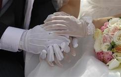 <p>Selon une étude menée durant 12 ans aux Etats-Unis, les hommes mariés se comportent mieux socialement que les célibataires. Les auteurs de l'étude attribuent ce résultat aux qualités intrinsèques de départ des hommes qui les ont rendu plus séduisants aux yeux de leurs futures épouses et au mariage qui les assagit. /Photo d'archives/REUTERS/Lee Jae-Won</p>