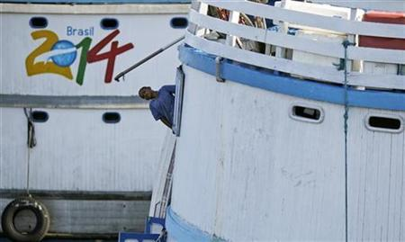 A boy looks out from the window of a boat, with a Brazil's FIFA World Cup Soccer 2014 logo, before a travel on the Negro river, at the Manaus port in northern Brazil, July 24, 2010. REUTERS/Ricardo Moraes