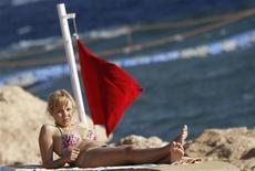 <p>Туристка лежит на пляже под флагом, предупреждающем о запрете на купание в Красном море, 06 декабря 2010 года. Египет в воскресенье сообщил об открытии пляжей для туристов после серии нападений акул, произошедших за последние две недели, в результате которых один человек погиб и четверо получили травмы. REUTERS/Amr Abdallah Dalsh</p>