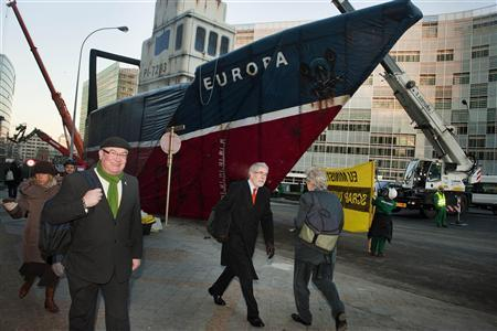 People walk past a giant model of a fishing trawler put up by Greenpease activists outside the European Council building where European Union Fisheries and Agriculture Ministers have gathered to decide on fishing quotas for 2011, in Brussels December 13, 2010. REUTERS/Eric De Mildt/Greenpeace/Handout
