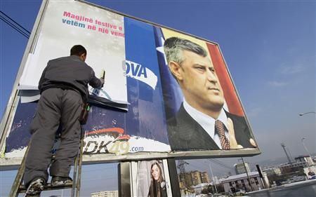 A worker removes an election billboard of Kosovo's Prime Minister Hashim Thaci after Sunday's polls, in Pristina December 15, 2010. REUTERS/Hazir Reka