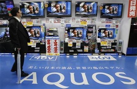A man looks at Sharp Corp's Aquos liquid-crystal display (LCD) televisions at an electronic store in Tokyo April 27, 2010. REUTERS/Yuriko Nakao