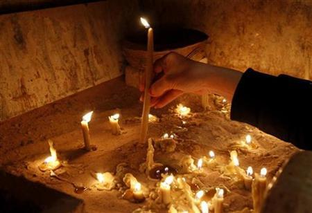 Iptisam, an Iraqi Christian woman, lights candles for victims of the attack on Our Lady of Salvation church of Baghdad, during a mass at an Orthodox church in Amman November 7, 2010. REUTERS/Ali Jarekji