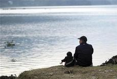 <p>Khagendra Thapa (L) and his mentor and the President of Khagendra Foundation sit by the Fewa Lake in Pokhara West Nepal October 12, 2010. REUTERS/Gopal Chitrakar</p>