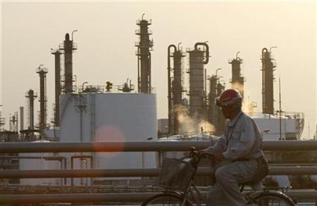 A worker rides past an oil factory at Keihin industrial area in Kawasaki, south of Tokyo in this October 23, 2009 file photo. REUTERS/Issei Kato