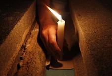 <p>Мужчина ставит свечу на могилу во время Дня памяти усопших на Кубе 2 ноября 2010 года. Фронтмен популярной в Советском Союзе западногерманской диско-группы Boney M Бобби Фаррел в четверг был найден мёртвым в номере отеля в Санкт-Петербурге, на другой день после концерта, сообщил агент музыканта. REUTERS/Enrique De La Osa</p>