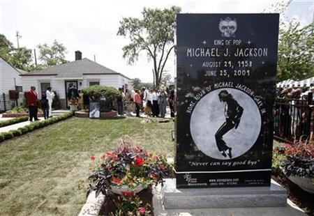 People gather outside the childhood home of pop star Michael Jackson in Gary, Indiana June 25, 2010. from Asia to the United States. REUTERS/John Gress